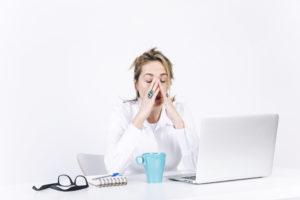 Mujer cansada y de mal humor junto a mesa con gafas taza y ordenador encima