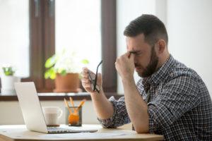 Hombre estresado masajeando el puente de la nariz que sufre de dolor de cabeza