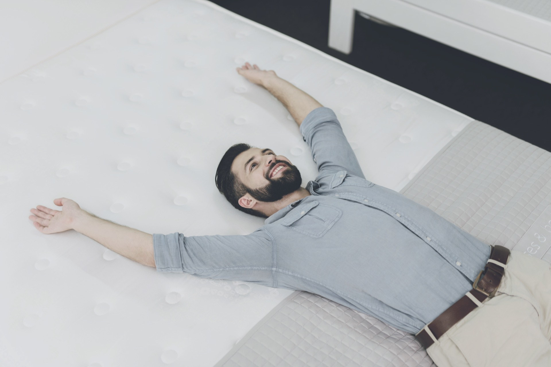 A Man Chooses A Mattress For Himself In The Store.