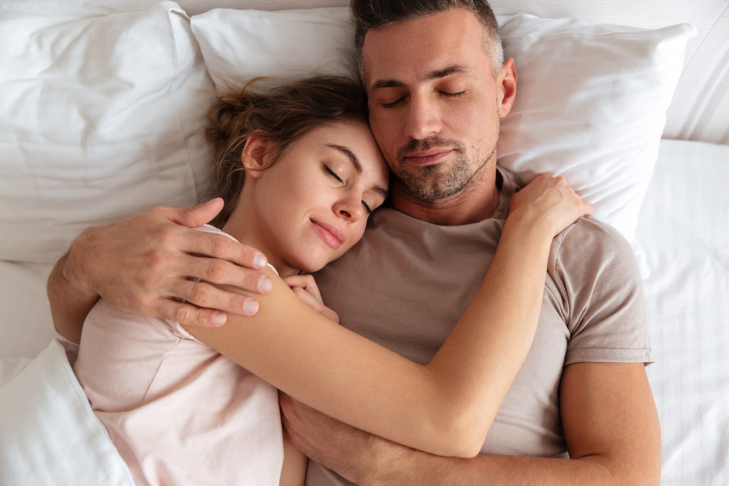 Top View Of Pretty Loving Couple Sleeping Together In Bed